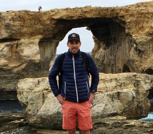 Julien qui regarde l'objectif avec en fond des roches de la côte basque