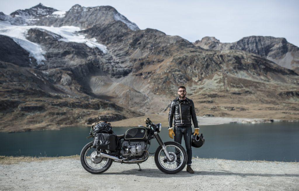 Loic qui pose avec une moto avec en fond de l'eau et des montagnes